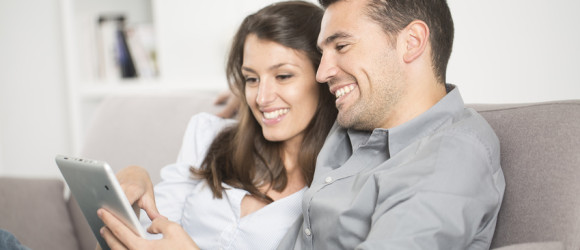 young couple using tablet pc at home